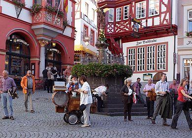 Urlaub an der Mosel: Die Moselregion kennenlernen und Bernkastel-Kues besichtigen. Zu sehen ist ein Spielmann auf dem historischen Marktplatz.